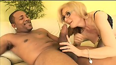 Busty blonde milf in sexy lingerie invites a black stud to fill her holes with his rod
