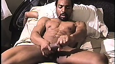 Hunky black guy lies on the bed and strokes his huge cock to pleasure