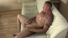 Sexy tattooed stud lies on the couch and jerks his cock until he cums