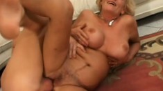 Big breasted blonde granny has a young guy taking care of her desires