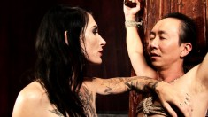 Skinny Asian slave's cock is wrapped in chains by a brunette domme